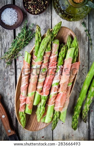 Fresh organic asparagus wrapped in prosciutto on a cutting board top view - stock photo