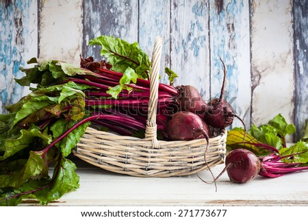Fresh organic beetroot with green leaves in a basket - stock photo