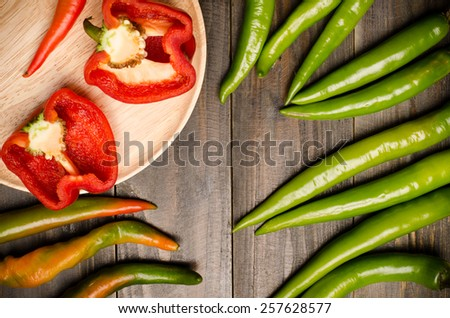 Fresh organic bell pepper on wooden plate and green pepper on black wooden background - stock photo