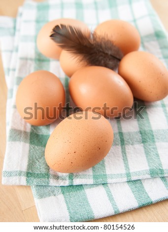 Fresh Organic Brown Eggs on Kitchen Table with One Feather - stock photo