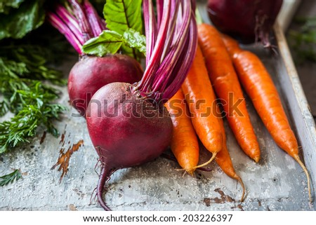 Fresh organic carrots and beetroot  on old wooden board - stock photo