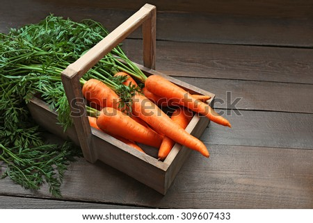 Fresh organic carrots in crate on wooden background - stock photo
