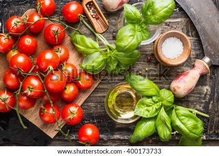 Fresh organic cherry tomatoes with basil leaves and olives oil on rustic kitchen table, top view - stock photo