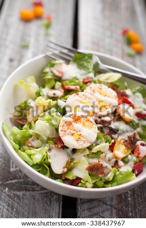 Fresh organic Cobb salad topped with homemade Ranch dressing, hard boiled eggs, bacon, peppers, peas, and green onions on an old weathered barn wood table - stock photo