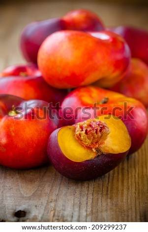 fresh organic flat nectarines on a rustic wooden background - stock photo