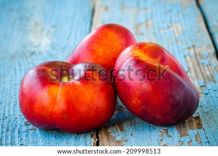 fresh organic flat nectarines on an old rustic background - stock photo