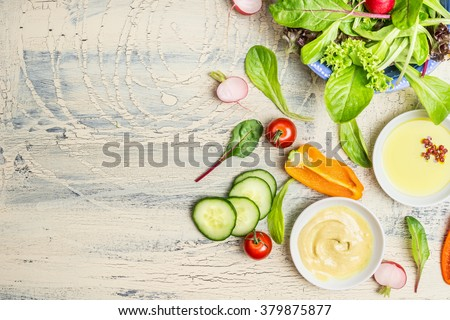 Fresh organic green salad preparation with oil and  dressing ingredients on light rustic background, top view, place for text. Healthy lifestyle or detox diet food concept - stock photo
