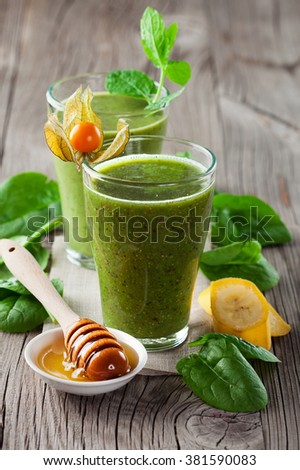 Fresh organic green smoothie in a glass with ingredients - spinach, banana and honey on old rustic  wooden background, selective focus - stock photo