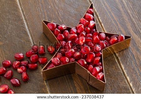 Fresh organic pomegranate seeds in copper star shape sitting on dark wooden table - stock photo