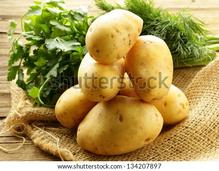 fresh organic potatoes on a wooden table - stock photo
