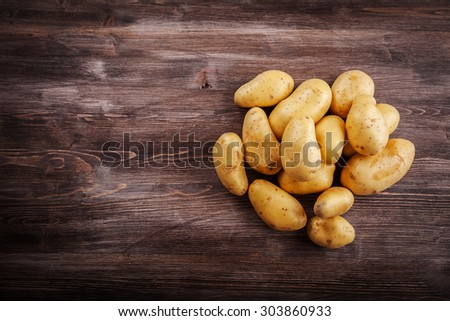 Fresh organic potatoes on a wooden table with copy space - stock photo