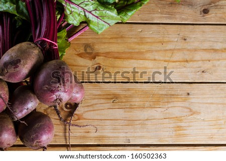 Fresh, organic raw beetroot against a wooden background. Plenty of copy space. - stock photo