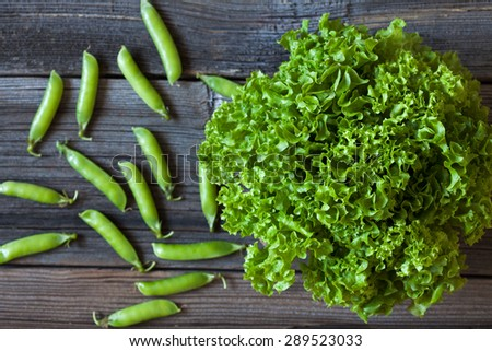 Fresh organic salad lettuce and green peas on vintage wooden background. Clean eating good food. Rustic style and natural light. - stock photo