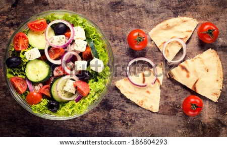 Fresh organic salad with vegetables and cheese from above on wooden background - stock photo