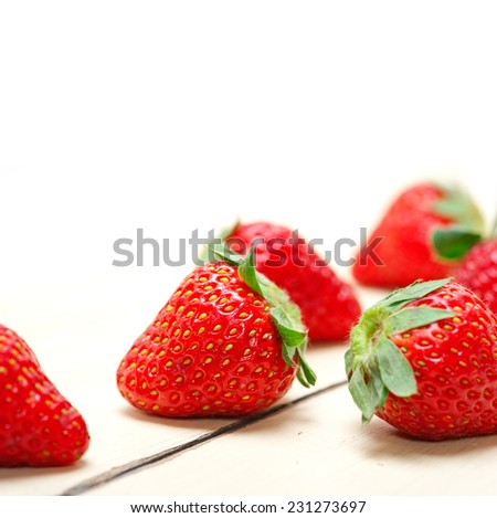 fresh organic strawberry over white rustic wood table - stock photo