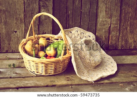 Fresh organic vegetables and a straw hat on a grunge wood background. - stock photo