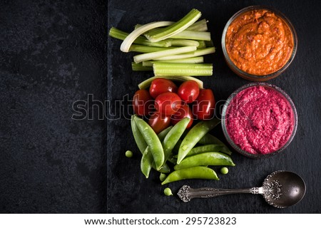 Fresh organic vegetables and vibrant dip selection, from above - stock photo