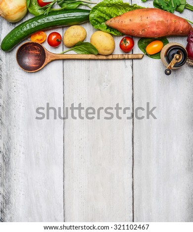 Fresh organic vegetables ingredients and wooden spoon on rustic wooden background, top view. Healthy eating concept. - stock photo