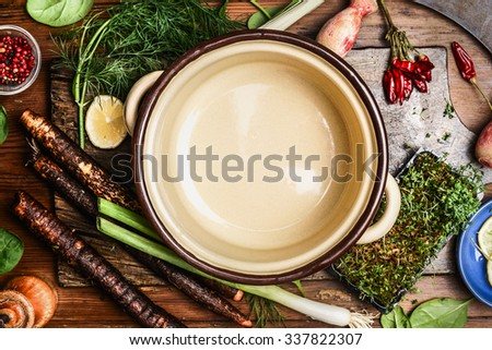 fresh organic vegetables ingredients for tasty cooking around empty cooking pan, top view. Healthy clean food or vegetarian cooking concept.  - stock photo