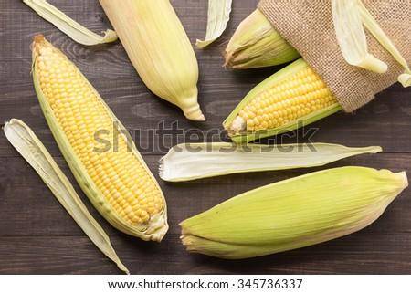 Fresh organic yellow sweet corn on wooden table. Top view. - stock photo