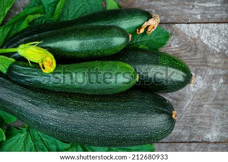 Fresh organic zucchini on the wooden table - stock photo