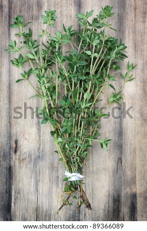 Fresh, organically grown thyme on an old wooden chopping board. - stock photo