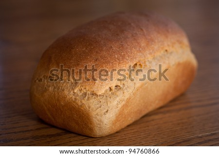 Fresh out of the oven loaf of homemade whole wheat bread on a wooden table - stock photo