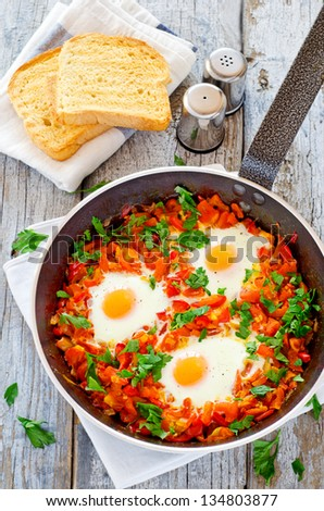 Fresh out of the oven poached eggs in tomato and red pepper sauce breakfast - stock photo