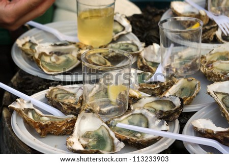Fresh oysters and white wine on french market - stock photo