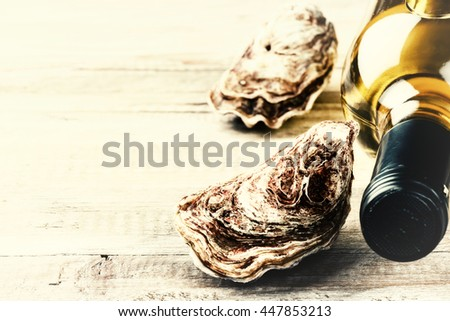 Fresh oysters with white wine bottle. Food background with copyspace  - stock photo
