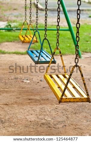 Fresh paint on the playground swings. - stock photo