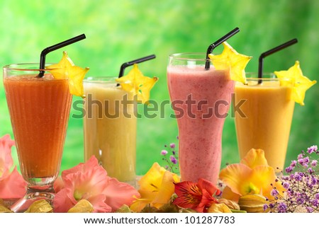 Fresh papaya, strawberry, pineapple and mango fruit juices and milkshakes with straws decorated with flowers (Selective Focus, Focus on the papaya and strawberry juices in the front) - stock photo