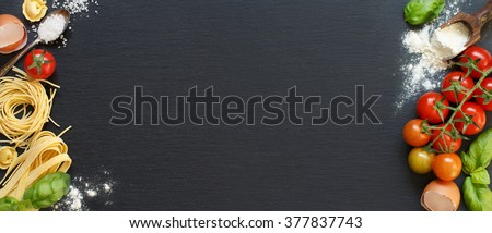 Fresh pasta and ingredients on a dark board top view - stock photo