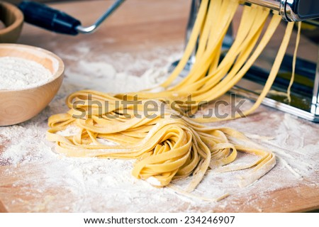fresh pasta and pasta machine on kitchen table - stock photo
