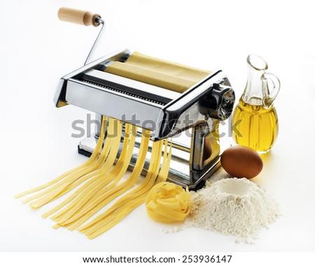 Fresh pasta cutting in machine on white background - stock photo