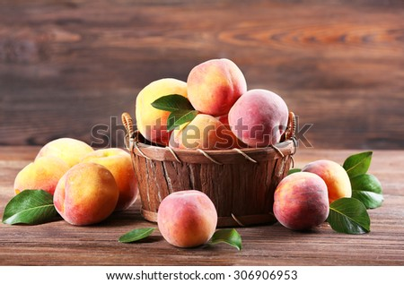 Fresh peaches in wicker basket on wooden background - stock photo