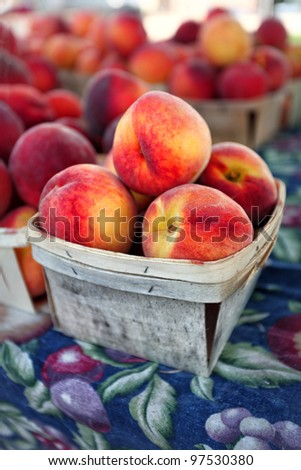 Fresh peaches in wooden basket at farmers market in chicago illinois - stock photo