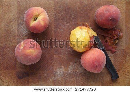 Fresh peaches on a wood cutting board, one being peeled with paring knife - stock photo