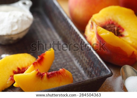 Fresh peaches sliced into a vintage pan with sugar and flour - stock photo