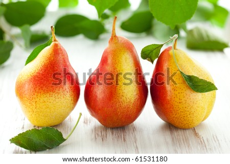 fresh pears with leaves  on the white wooden  table - stock photo