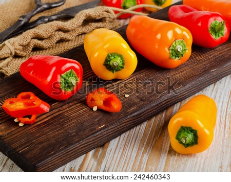 Fresh peppers on  cutting board. Selective focus - stock photo