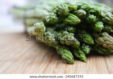 Fresh picked asparagus on a wooden cutting board  - stock photo
