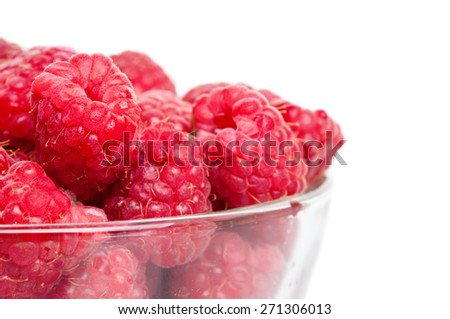 Fresh picked ripe red organic raspberries in glass bowl on white background. Selective focus on the front berry - stock photo