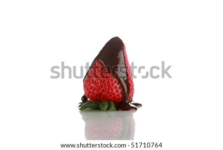 fresh picked strawberry with warm chocolate sauce being drizzled upon it on white with nice reflections - stock photo