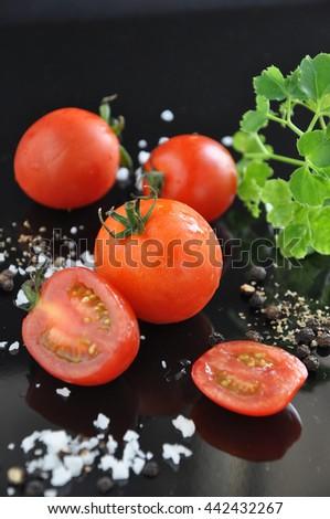 Fresh pieces of cherry tomato on black background - stock photo