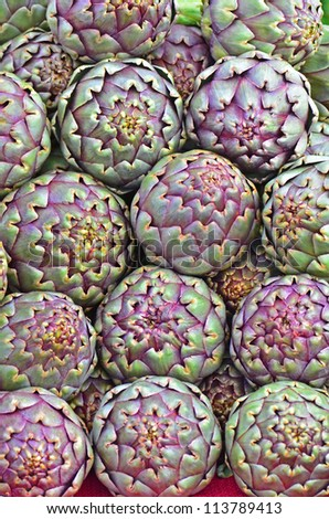 Fresh pile of Italian Artichokes on display at a local farmers market ready for the picking. - stock photo