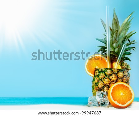 Fresh pineapple with oranges, tubules and ice on sunny beach with copy space - stock photo