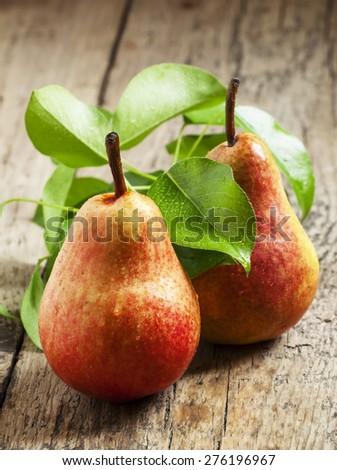 Fresh pink pear with drops of water on wooden table, selective focus - stock photo
