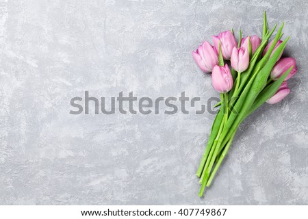 Fresh pink tulip flowers on stone table. Top view with copy space - stock photo