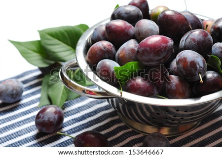 Fresh plum in metal bowl on wooden background - stock photo